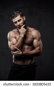 Handsome and haired man with nude torso and muscular build posing with hand under his chin in dark background.