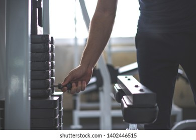 Handsome hand change weight on Iron heavy plates stacked of weight machine in gym.