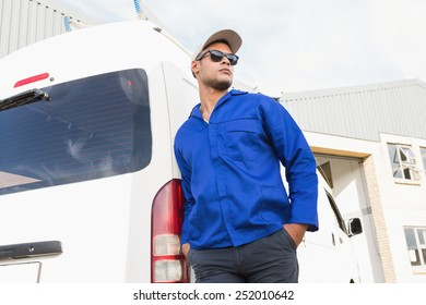 Handsome handyman posing with sunglasses leaning against his van