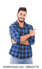 Handsome happy beard young man smiling and pointing to something, guy wearing blue caro shirt and jeans, isolated on white background