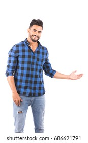 Handsome happy beard young man smiling and showing something, guy wearing blue caro shirt and jeans, isolated on white background