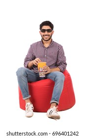 Handsome happy beard young man with a cinema glasses sitting on a red chair and eating popcorn, guy wearing caro shirt and jeans, isolated on white background