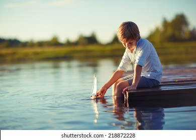 A handsome happy child playing with a tiny boat on water on a sunny summer day. Kids in country. Nature.