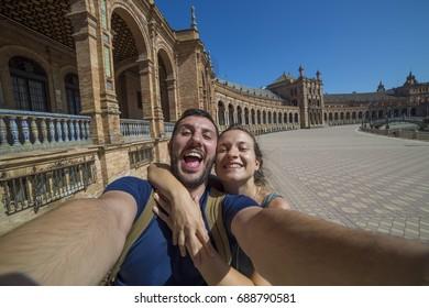 handsome happy couple take photo selfie in Spain Square (Plaza de Espana), Seville, Spain, during a world trip tour