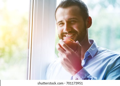handsome happy man eating apple