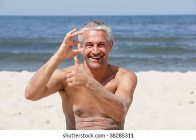 Handsome happy man giving thumbs up and OK sign on the beach