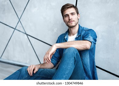 Handsome happy man sitting at the floor over gray background.
