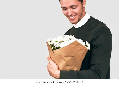 Handsome happy man smiling delivering a bouquet of white flowers. Attractive male model with a bunch of flowers preparing for a date with girlfriend. Valentine's Day. Mother's Day concept