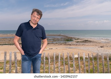 Handsome happy man standing on beach in Isle de Re France