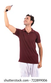 Handsome happy man wearing red t-shirt and white short, guy smiling and taking a selfie, isolated on white background