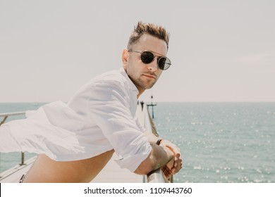 Handsome happy man wearing white shirt and sunglasses at the sea or the ocean background.Travel vacation holiday concept