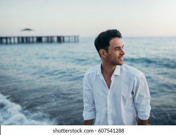 Handsome happy man wearing white shirt at the sea or the ocean background. Travel vacation holiday. Man walking at the sea, enjoy tropical season. Relax caucasian adult man looking away at sunset..