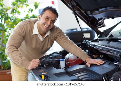 Handsome happy mature man smiling to the camera joyfully while examinign an engine of an automobile at the dealership showroom copyspace hobby mechanic repair driving ownership powerful transport.