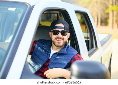 Handsome happy men driver with a beard smiling in the pickup car truck. Attractive male driving big vehicle, wearing hat, checkered shirt and black sun glasses. Sunny weather, summer