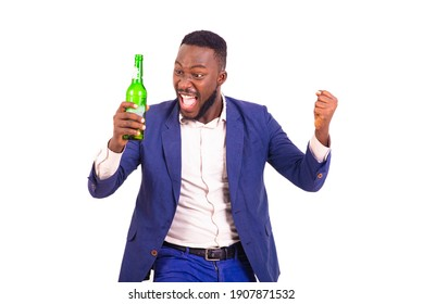 handsome happy young businessman wearing elegant suit and holding beer bottle while making winning gesture with raised arm.