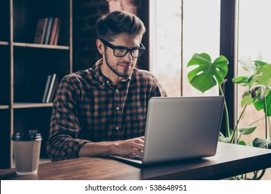 Handsome happy young man in glasses typing on laptop