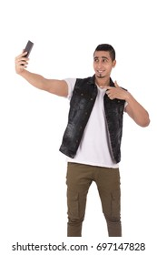 Handsome happy young man smiling and taking selfie, guy wearing casual vest and jeans, isolated on white background
