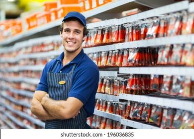 handsome hardware store salesman standing next to fasteners shelf