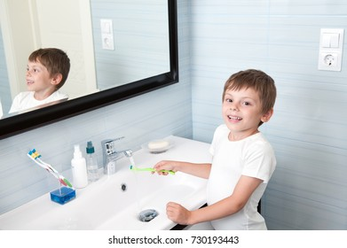handsome healthy boy washing toothbrush over washbasin in blue bathroom