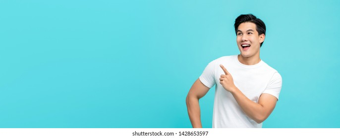 Handsome healthy young Asian man smiling with his finger pointing isolated on light blue banner background with copy space