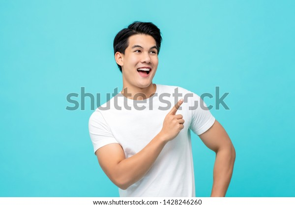 Handsome healthy young Asian man smiling with his finger pointing isolated on light blue studio background