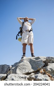 Handsome hiker standing at the summit on a sunny day