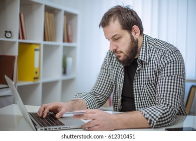 Handsome hipster bearded man working in office alone
