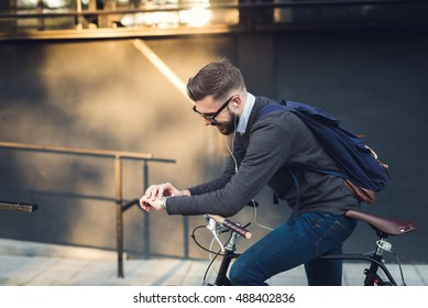 Handsome hipster enjoying a bike ride and checking time on his watch.
