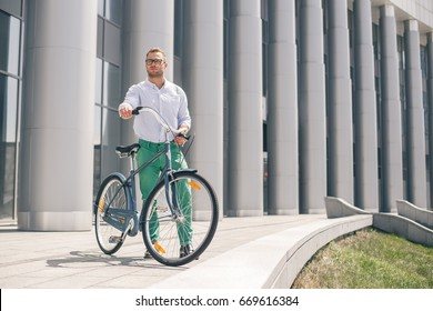 Handsome hipster enjoying city ride by bicycle. Businessman and his bicycle on city streets. The concept of the modern lifestyle of young men.