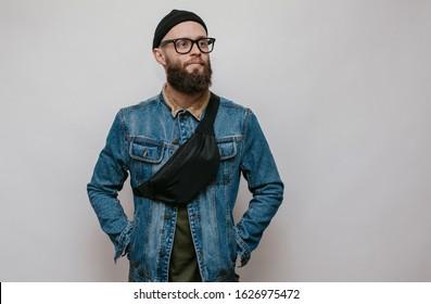 Handsome hipster guy with beard wearing blue denim jacket and waist bag. Mockup for print