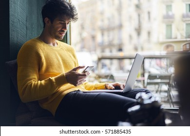 Handsome hipster guy monitoring morning news on websites choosing main theme for front page using smartphone and wireless connection in cozy coffee shop interior, male freelancer using laptop computer