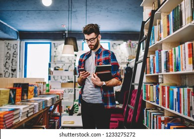 Handsome hipster guy in spectacles making money transaction for buying new bestseller via mobile phone, caucasian stylish man spending time in bookstore while browsing internet on smartphone