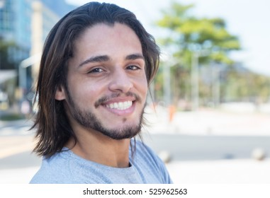 Handsome hipster with long brunette hair in the city