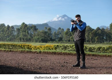 Handsome hipster male holding camera with beautiful volcano in background