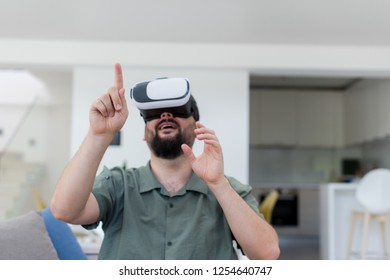 handsome hipster man with beard trying vr glasses at modern home
