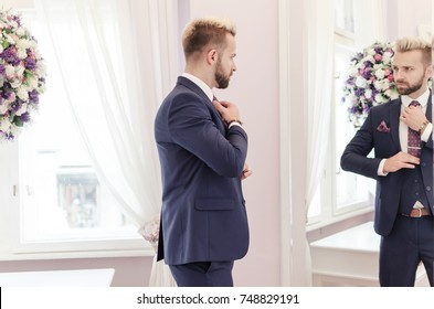 Handsome hipster man fix his tie and watching himself in the mirror, studio shooting. Businessman in suit