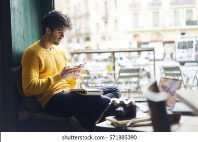 Handsome hipster man receive messages from friend texting answer while chatting through application on smartphone connected to free 5G wireless, male photographer using gadgets in cozy coffee shop