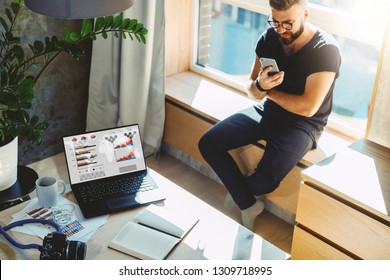 Handsome hipster man sits home on windowsill, reads text messages, sends email, uses his phone and fast internet connection. On table laptop with graphs, charts, diagrams on monitor, camera, notebook.