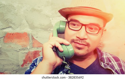 handsome hipster man talking with retro phone on the brick background