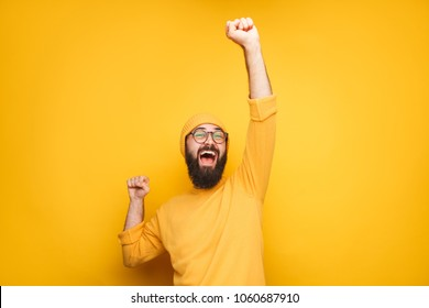 Handsome hipster man in yellow holding hands up in victorious gesture on yellow background.
