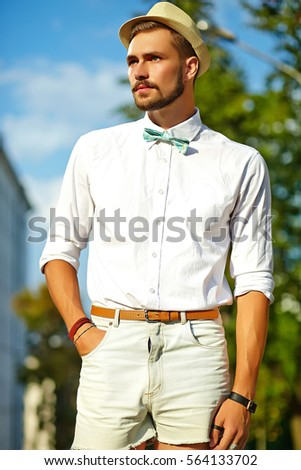 2e32f83eec56 Handsome hipster model man in stylish summer clothes posing on street  background in hat