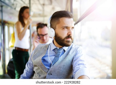 Handsome hipster modern man with headphones traveling by tram in town