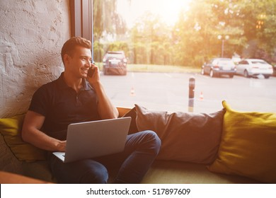 handsome hipster modern man working home using laptop besides a large window with film flare effect