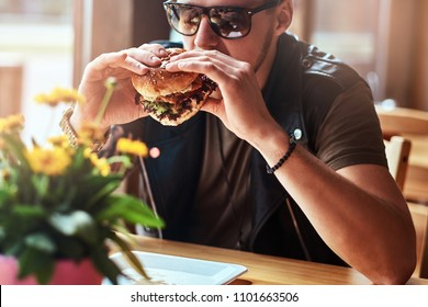 Handsome hipster with a stylish haircut and beard sits at a table, decided to dine at a roadside cafe, eating a hamburger.