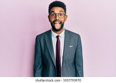 Handsome hispanic business man with beard wearing business suit and tie sticking tongue out happy with funny expression. emotion concept.