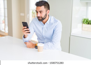 Handsome hispanic business man drinking coffee and using smartphone with a confident expression on smart face thinking serious