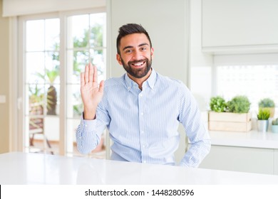 Handsome hispanic business man Waiving saying hello happy and smiling, friendly welcome gesture