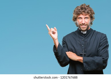 Handsome hispanic catholic priest man over isolated background with a big smile on face, pointing with hand and finger to the side looking at the camera.