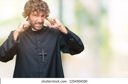 Handsome hispanic catholic priest man over isolated background covering ears with fingers with annoyed expression for the noise of loud music. Deaf concept.