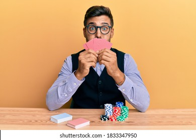 Handsome hispanic croupier man sitting on the table with poker chips and cards puffing cheeks with funny face. mouth inflated with air, catching air.